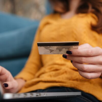 Close up of a woman buying on line with bank card and laptop while sitting in the living room at home