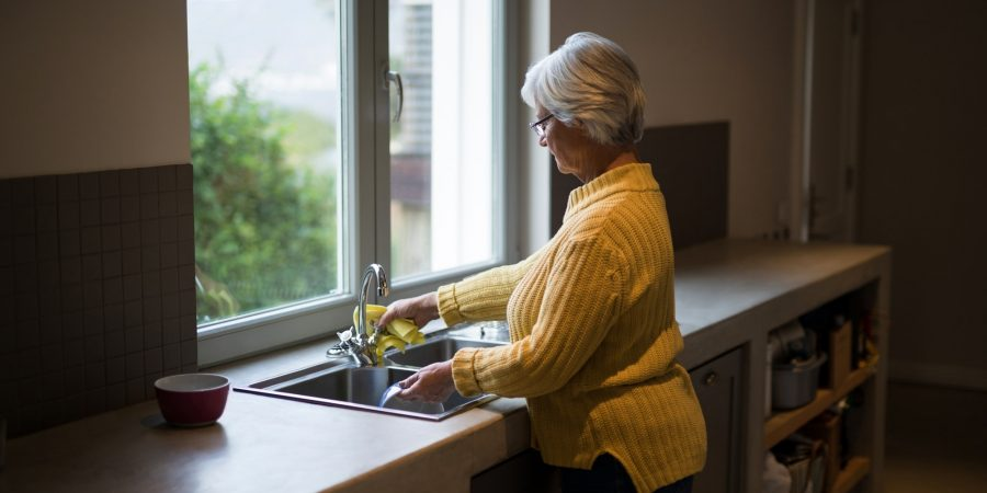 Senior woman washing dish in kitchen sink at home